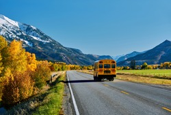 School bus on highway in Colorado Rocky Mountains at autumn, USA. Mount Sopris landscape.