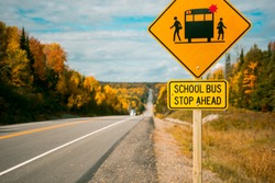 School bus stop ahead road sign. Yellow warning sign on the roadside. Canada's highway