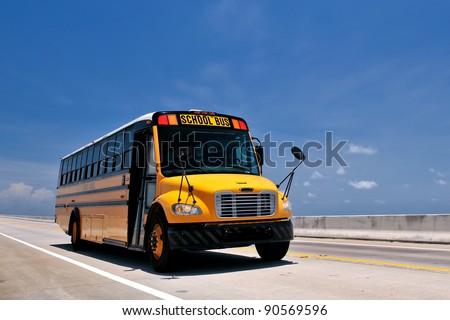 school bus traveling on florida's overseas highway from low angle against blue sky