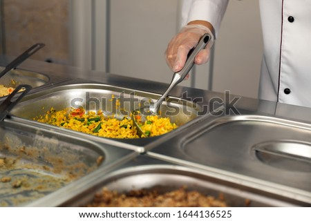 School canteen worker at serving line, closeup. Tasty food Photo stock ©