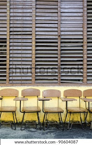 School chair-desks outside classroom with wooden jalousie windows