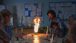 School Chemistry Classroom: Engrossed Children Watch How Enthusiastic Teacher Shows Science Experiment by Setting Powder on Fire Creating Beautiful Fireworks. Kids Getting Fun Modern Education