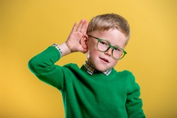 School child boy holds hand near ear. Funny boy in green glasses and sweater  listens carefully. Family communication with kid. Hear parent. Interesting education news