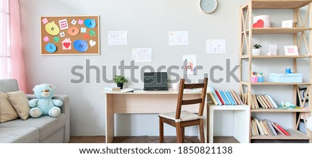 School child room interior space with table, couch, bookcase, books and laptop on table indoors at home apartment background. Children homeschool, online distance remote virtual learning, banner.