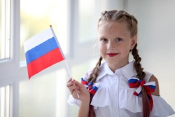 School child stands and holds the flag of Russia. Little girl with face painting of Russian symbolism. Russian flag day.