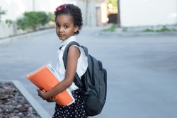 School child with a backpack holding an orange folder. Mix races kid portrait. Eye contact. Outdoors. Standing alone on the road. Back to school, childhood, off-line learning concept. Copy space.