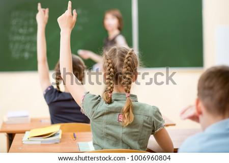 School children in classroom at lesson. Teacher standing at chalkboard.