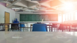 School classroom closed in blur background without young student; Blurry view of empty examination class room no kid or teacher with chairs and tables in campus university.