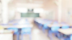 School classroom in blur background without young student; Blurry view of elementary class room no kid or teacher with chairs and tables in campus.