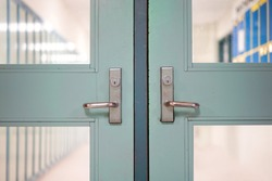 School closed due to Coronavirus.  School closure under COVID-19 global pandemic. Selective focus on door and handle with blurred hallway, locker background. Fight against public health risk disease.