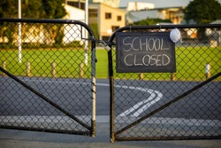 school closed sign with protective mask hanging on a padlocked gate, school closed or shutdown concept amid coronavirus fears and panic over contagious virus spread of the pandemic outbreak