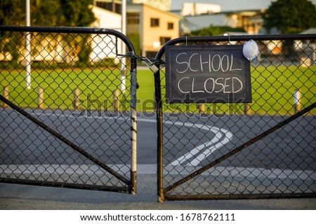 Photo of  school closed sign with protective mask hanging on a padlocked gate, school closed or shutdown concept amid coronavirus fears and panic over contagious virus spread of the pandemic outbreak