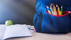 School concept, blue backpack with pencils on the table in front of the chalk board stands on the table with notebooks, apples, paints, extra wide banner with copy space