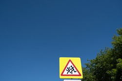 School crossing sign, roadsign with warning for crossing children. Blue sky background