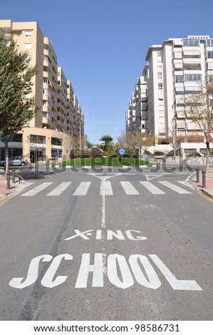 School Crossing Traffic sign Pedestrian Crosswalk on street of Urban City Highrise Residential area - stock photo