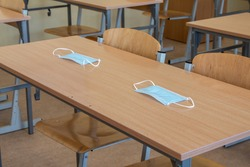 School desk in a school classroom with a face mask. School safety during a pandemic