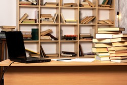 School desk with books and laptop on the background of a bookcase. workplace office worker. table with papers and pen. e-education concept. office in the house