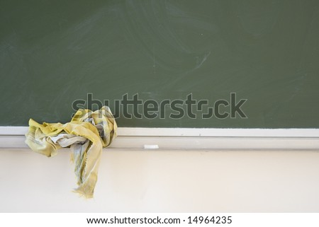 School desk with chalk on the shelf and copyspace - stock photo