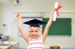 school, education and learning concept - happy little girl in bachelor hat or mortarboard with diploma celebrating success over classroom background