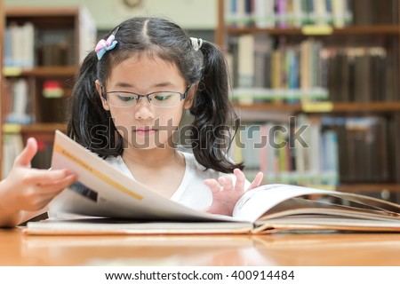 School education and literacy concept with young Asian girl student, smart kid in elementary grade learning, studying hard or reading children's picture book in library or classroom