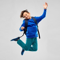 school, education and people concept - happy smiling student boy with bag jumping over grey background