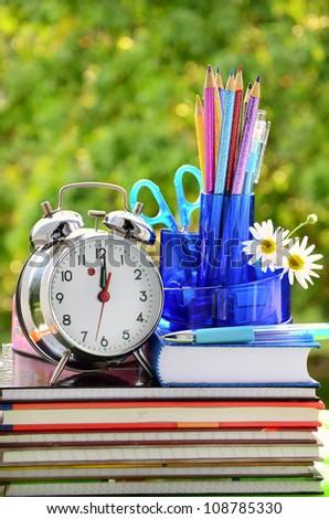 school equipment and alarm clock against green trees