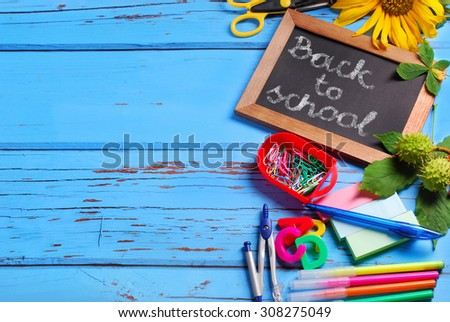 school equipment border with text  Back to school written by chalk on small blackboard  on blue wooden background