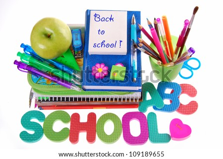"school equipment with color pencils ,ball pens,books,letters,apple and text ""back to school"" written on white board"