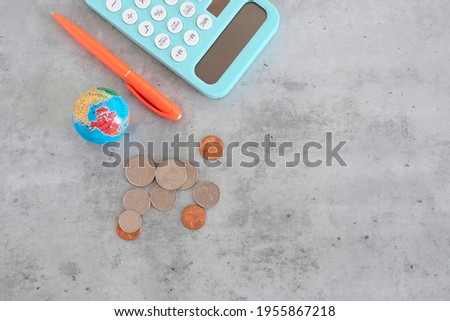 School fees concept. Budgetary item for expenditure on school education. Calculator, pen, coins of American origin on a gray background. View from above. Place for  text. Globe as a symbol of world.  Stock photo ©