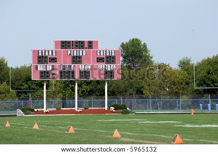 School football field with scoreboard in daytime.