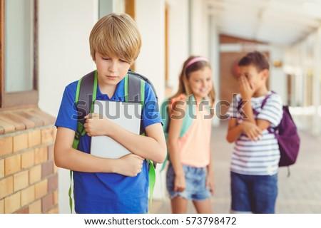 School friends bullying a sad boy in corridor at school