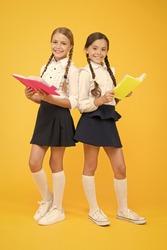 School friendship. Girl with copy books or workbooks. Study together. Kids cute students. Schoolgirls best friends excellent pupils. Schoolgirls wear school uniform. Knowledge day. School day