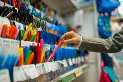 School girl choosing a pen in stationery store