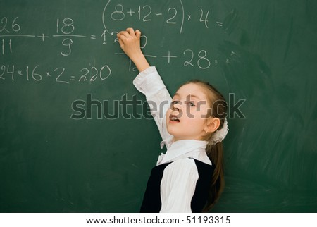 school girl finding solution and solving task on the  blackboard