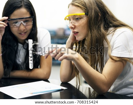 School girl friends learning science in the lab classroom