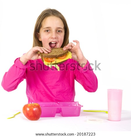 school girl is eating a healthy lunch with fruit and whole meal bread