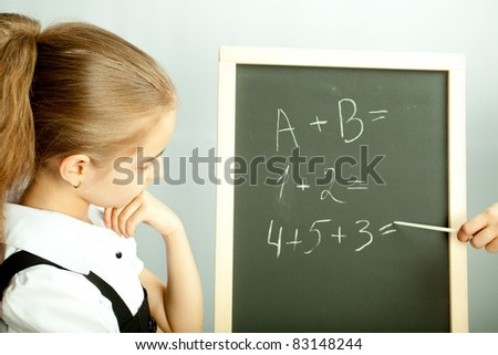 School girl looking at the blackboard with exercises and thinking about answers