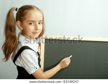 School girl near blank blackboard. Ready for writing. - stock photo