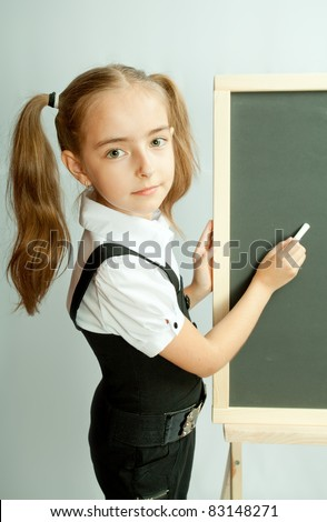 School girl near blank blackboard. Ready for writing.