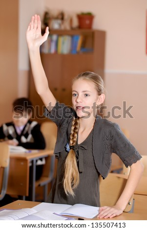 school girl sitting at desk  and raising hand
