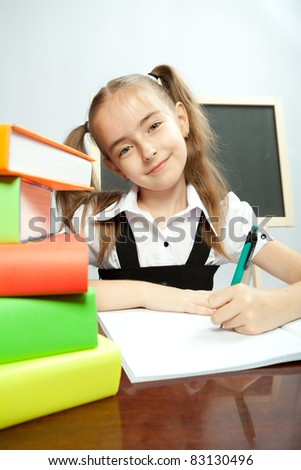 School girl sitting on the table with books. Writing in copybook.