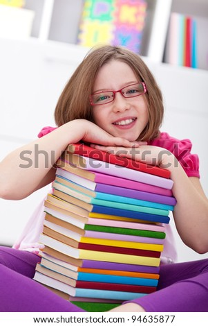 School girl sitting with lots of books smiling