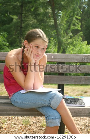 School girl thinking and working on difficult homework assignment in a park on a bench