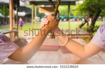School girl Two people are resting With a light arm exercise and arm wrestle while staying at noon. Foto stock ©