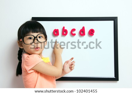 School girl wears a big spectacles posing next to a white board