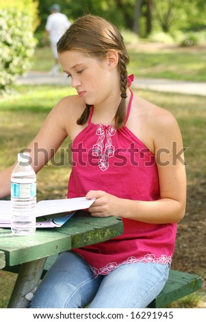 School girl writing in notebook, planner in an outdoors setting