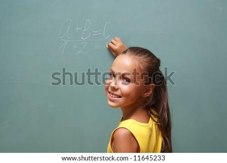 School girl writing on chalk board