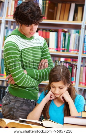 School guy looking at the book while his classmate looking - stock photo