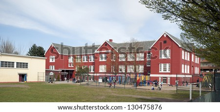 School - historic red America's brick school with playground and students