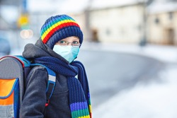 School kid boy with glasses wearing medical mask on the way to school. Child backpack satchel. Schoolkid on winter day with warm clothes. Lockdown and quarantine time during corona pandemic disease
